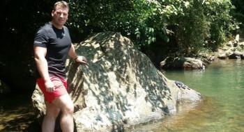 John Blackburn on holiday in summer gear in front of a rock