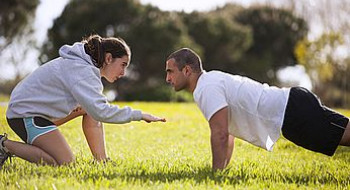 A man does push ups on some grass
