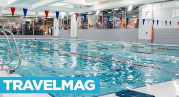 TravelMag logo over YMCA Club's swimming pool
